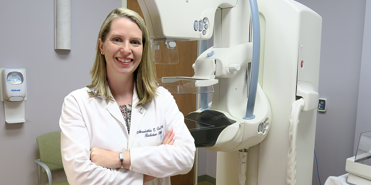 Radiation oncologist Amy Curtis, MD, poses with a 3D mammography machine that she uses for research on a clinical trial at Gibbs Cancer Center..