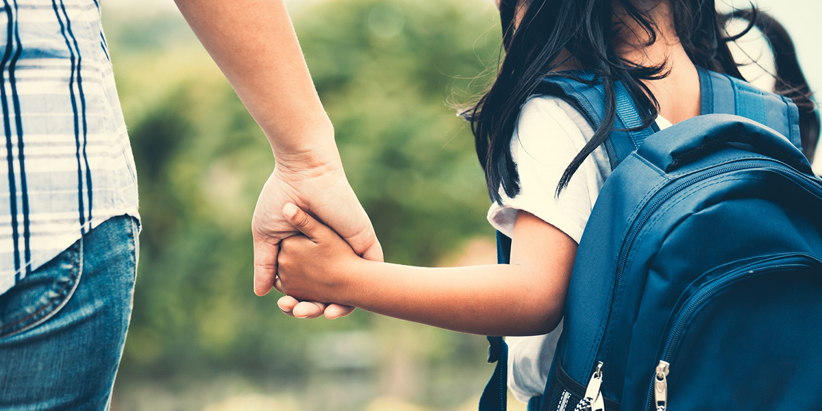 Midsection Of Mother Holding Daughter Hand While Taking Her To School