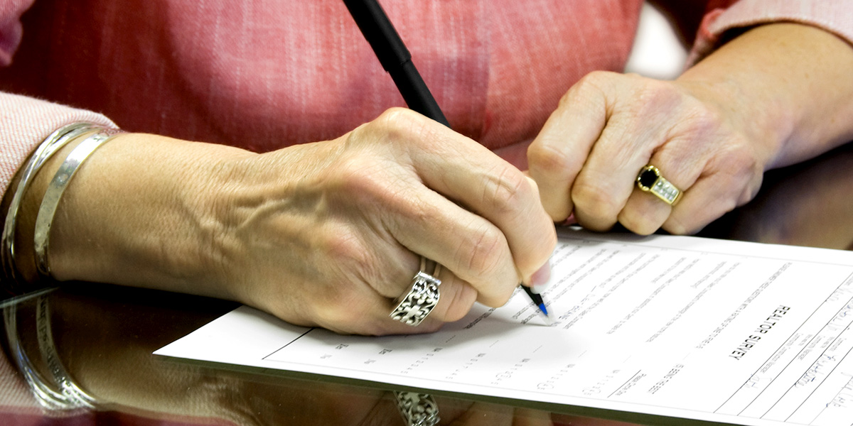 Mature woman's hands are signing end-of-life planning forms and documents