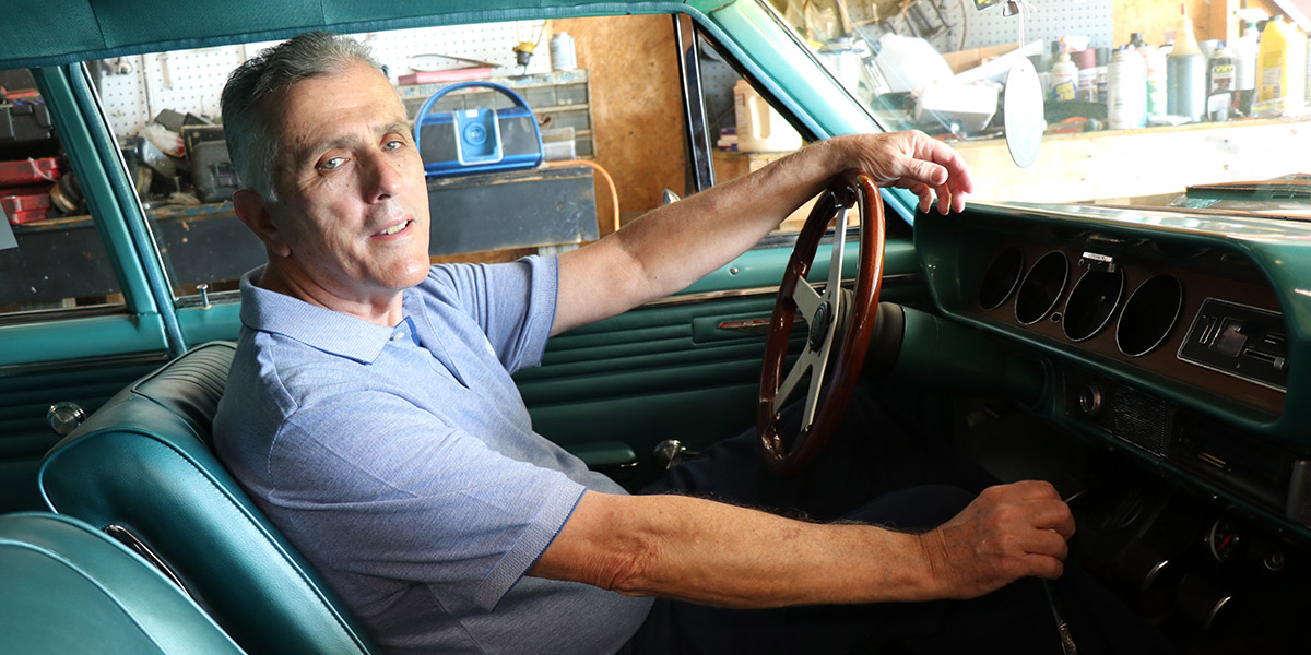 David Adkins, apatient who underwent the MitraClip procedure, sits in front of the steering wheel in a classic car
