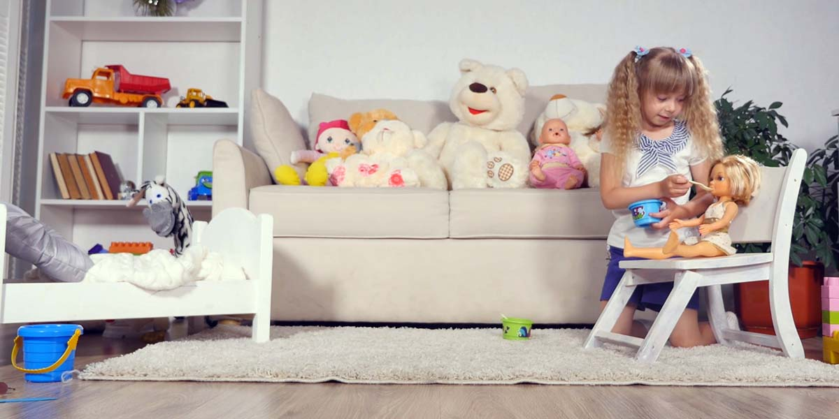 Little girl in a child's playroom filled with toys, feeding a babydoll
