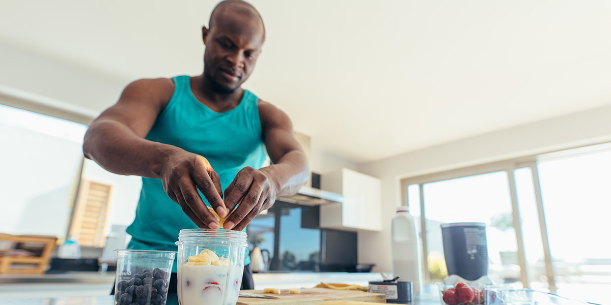 An athletic man adds healthy fruit into his smoothie to optimize his diet for sports performance.