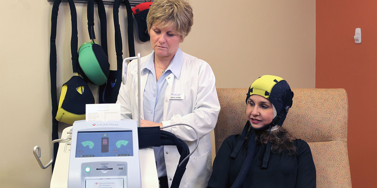 a doctor monitors a patient wearing the DigniCap Scalp Cooling System