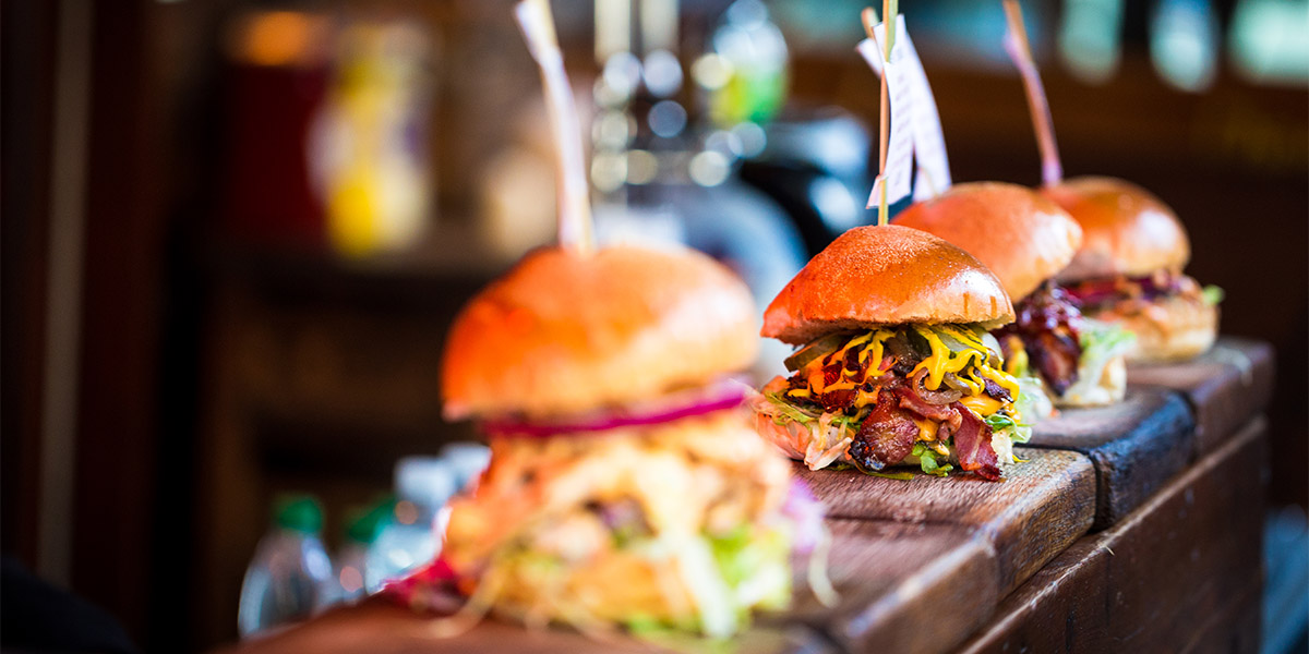 Three hamburgers loaded with various toppings sit on a bar top waiting to be taken out to diners