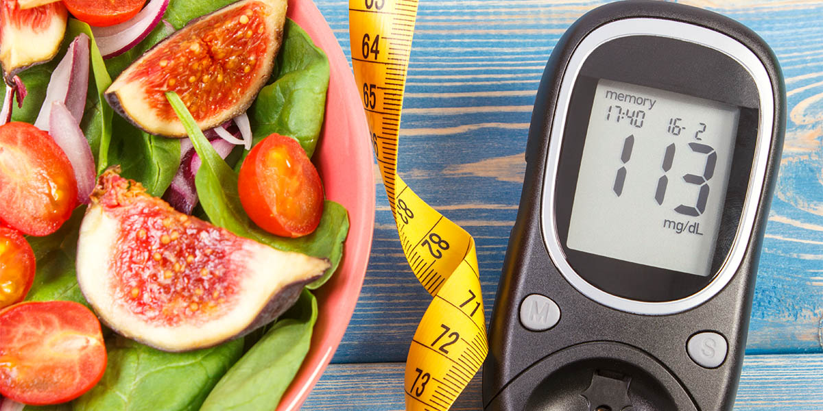 A salad, a measuring tape and a blood sugar measuring tool laying beside each other
