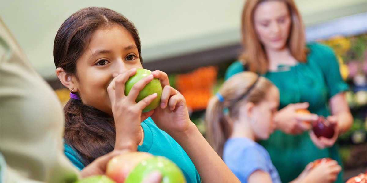 A child eats a green apple while a mother and child pick out red apples in the background