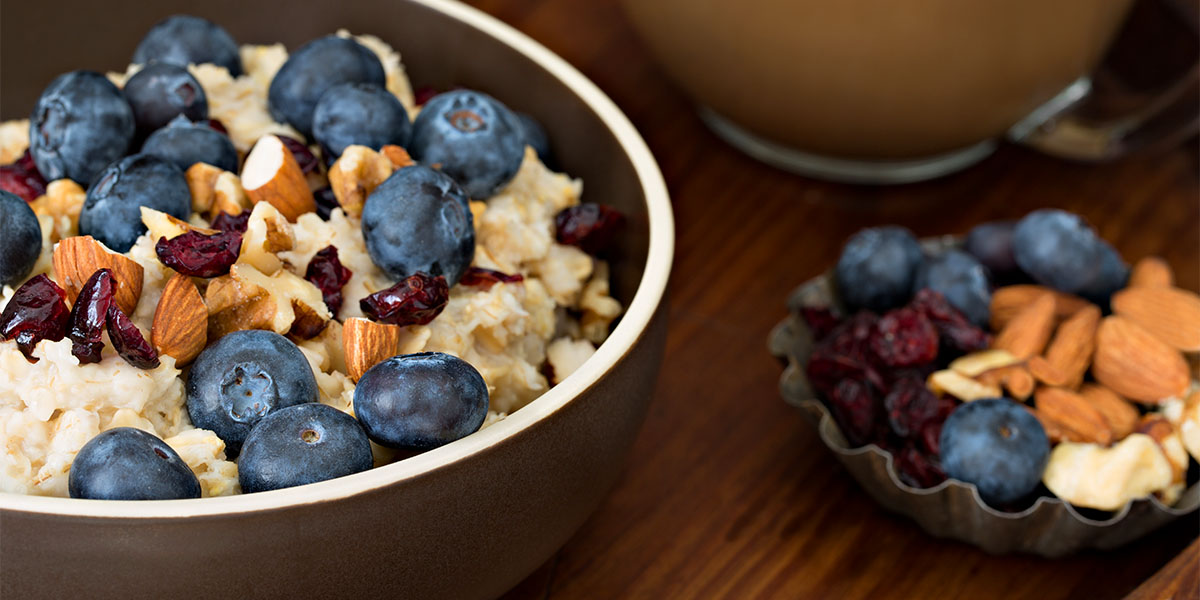 Closeup shot of a bowl of oatmeal with dried cranberries, blueberries and almonds on top